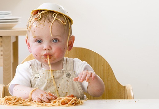 Messy baby boy in high chair with bowl of spaghetti on head